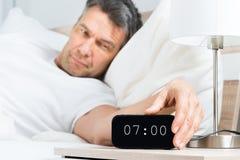 Reifer Mann, der Uhr abstellt Lizenzfreie Stockfotos