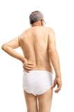 Reifer Mann in der Unterwäsche, die unter Rückenschmerzen leidet Lizenzfreie Stockbilder