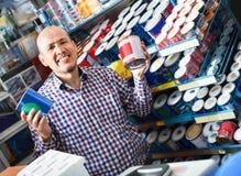 Reifer Mann, der Wandfarbe und -emulsion im Speicher vorwählt stockfotografie