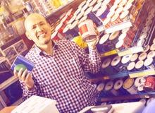 Reifer Mann, der Wandfarbe und -emulsion im Speicher vorwählt lizenzfreies stockfoto