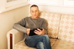 Reifer Mann, der zu Hause digitale Tablette verwendet Lizenzfreie Stockfotografie