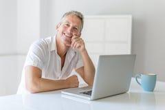 Reifer Mann, der zu Hause Laptop auf Schreibtisch verwendet lizenzfreie stockfotografie