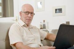 Reifer Mann, der zu Hause Laptop verwendet Stockbilder