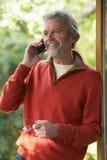 Reifer Mann, der zu Hause schnurloses Telefon verwendet Stockbild