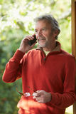 Reifer Mann, der zu Hause schnurloses Telefon verwendet Lizenzfreie Stockbilder