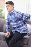 Reifer Mann, der zu Hause unter Rückenschmerzen leidet lizenzfreies stockfoto