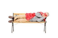 Reifer Mann im Superheldkostüm schlafend auf Bank Lizenzfreies Stockfoto