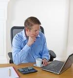 Reifer Mann konzentrierte sich auf Laptopschirm beim Arbeiten Lizenzfreies Stockfoto