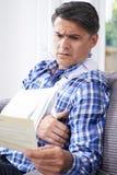 Reifer Mann-Lesebuchstabe über Verletzung stockbild
