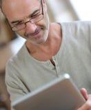 Reifer Mann mit Brillen ebook lesend stockfotos