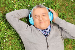 Reifer Mann mit den Kopfhörern, die auf Gras liegen stockbild