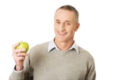 Reifer Mann mit einem Apfel Stockfoto