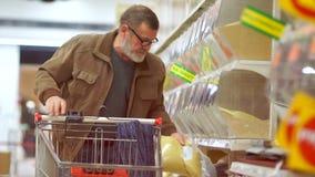 Reifer Mann mit einem Bart kauft Getreide in einem Supermarkt, der Pensionär einsetzt die Tasche in den Wagen Vater `s Tag stock video