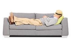 Reifer Mann mit Hut über seinem Kopf, der auf einem Sofa schläft Lizenzfreies Stockbild