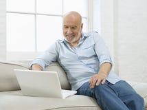 Reifer Mann mit Laptop auf Sofa Stockfotografie