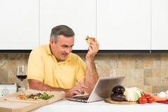 Reifer Mann mit Laptop in der Küche Stockfoto