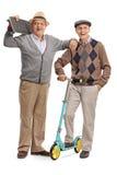Reifer Mann mit Skateboard und ein anderer Mann mit Roller Stockfotografie