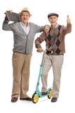 Reifer Mann mit Skateboard und Mann, der Daumen aufgibt Stockfotos