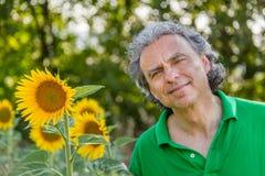Reifer Mann nahe Sonnenblumen Lizenzfreie Stockfotografie