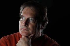 Reifer Mann schaut - auf schwarzem Hintergrund fragend lizenzfreies stockbild