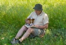 Reifer Mann und junger Hund, die interessantes Buch liest Lizenzfreies Stockbild