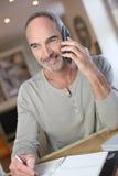 Reifer Mann zu Hause, der auf Smartphone spricht Lizenzfreies Stockbild