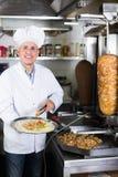 Reifer Mannchef, der köstlichen Kebab vorbereitet Lizenzfreie Stockfotografie