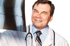 Reifer männlicher Radiologe, der den Röntgenstrahl des Patienten studiert Stockbild