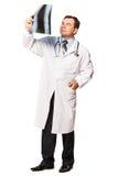 Reifer männlicher Radiologe, der den Röntgenstrahl des Patienten studiert Stockfotografie