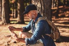 Reifer männlicher Wanderer, der digitale Tablette für Navigation verwendet Stockfoto