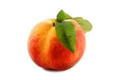 Reifer Pfirsich mit einem Blatt auf einem weißen Hintergrund Stockfotografie