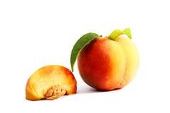 Reifer Pfirsich mit einem Blatt auf einem weißen Hintergrund Lizenzfreie Stockbilder