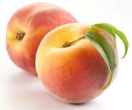 Reifer Pfirsich zwei mit Blättern Lizenzfreie Stockfotos