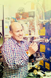 Reifer positiver Mann, der Heizwasserhahn im Speicher vorwählt lizenzfreies stockfoto