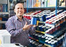 Reifer positiver Mann, der Wandfarbe und -emulsion im Speicher vorwählt stockfotografie