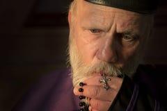 Reifer Priester, betend mit Rosenkranzperlen lizenzfreies stockfoto