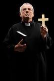 Reifer Priester, der ein Kreuz hält und oben schaut Stockfoto