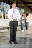 Reifer Professor With Books Standing auf College Lizenzfreie Stockbilder