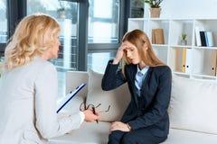 reifer Psychologe, der mit deprimierter junger Frau spricht Stockbild