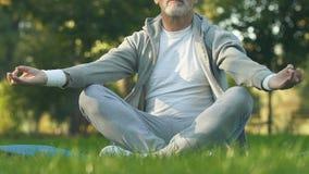 Reifer sportiver Mann, der in Lotussitz im Park, in der Erholung und in der Meditation sitzt stock footage