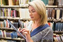 Reifer Student, der Tablette in der Bibliothek verwendet Lizenzfreie Stockfotografie