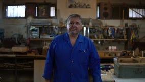 Reifer Tischler nähert sich der Kamera und steht in einer überzeugten Haltung in seiner Werkstatt stock footage