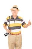 Reifer Tourist, der einen Daumen aufgibt Lizenzfreie Stockfotografie