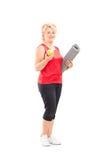 Reifer weiblicher haltener Apfel und eine trainierende Matte Stockfotografie
