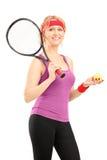 Reifer weiblicher Tennisspieler, der einen Schläger und eine Kugel anhält Stockbild