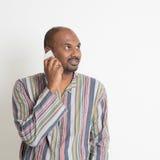 Reifer zufälliger indischer Mann, der auf Smartphone spricht Lizenzfreies Stockbild