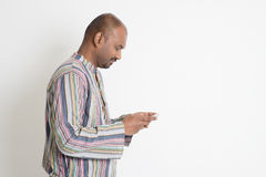 Reifer zufälliger indischer Mann, der Social Media verwendet Stockbild