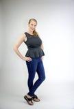 Reifes blondes weibliches Lächeln mit beiden Händen auf Hüften Stockfoto