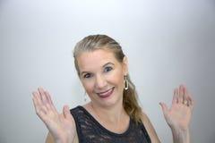 Reifes blondes weibliches Lächeln mit beiden Händen oben Lizenzfreie Stockbilder
