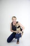 Reifes blondes weibliches Lächeln mit dem Hund, der Kamera gegenüberstellt Lizenzfreies Stockfoto